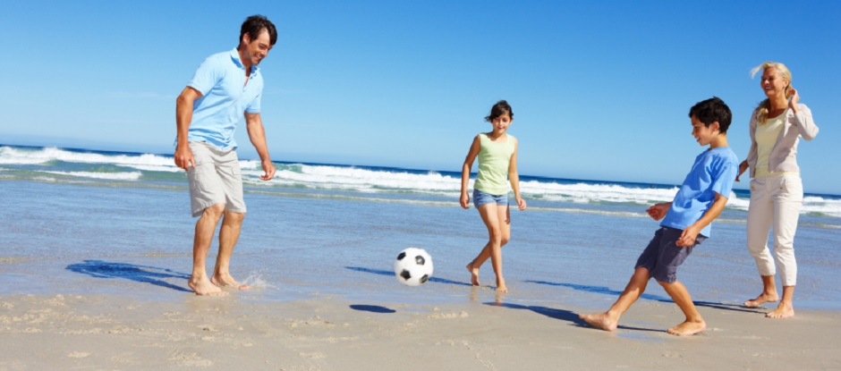 Mum, dad, daughter and son kick a football on the beach