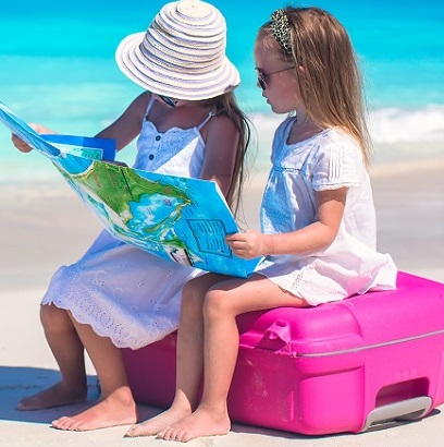 Little cute girls with big suitcase and a map on tropical beach