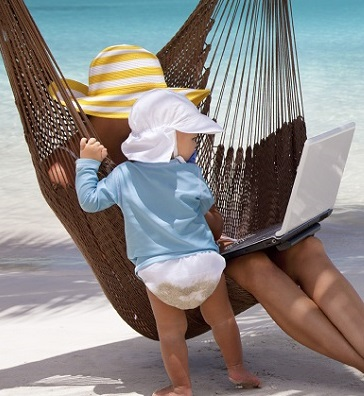 mother and child with laptop relaxing in a beach hammock