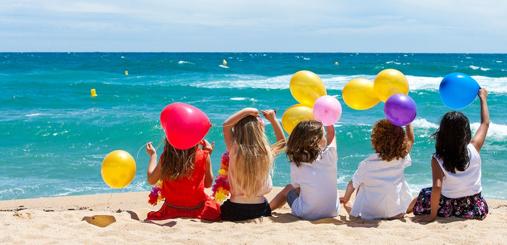 Top tips for travelling with children - kids with balloons on the beach