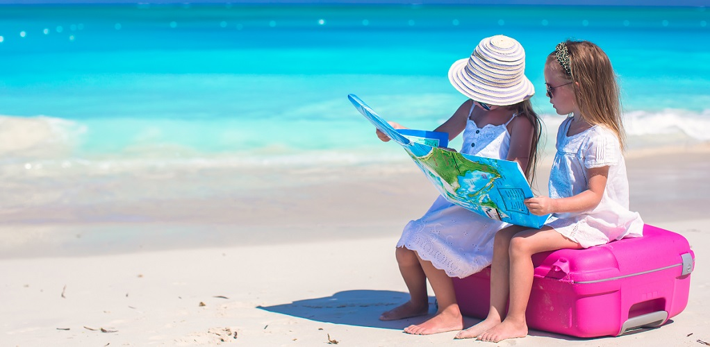 Top tips for travelling with kids - two girls with a suitcase on the beach